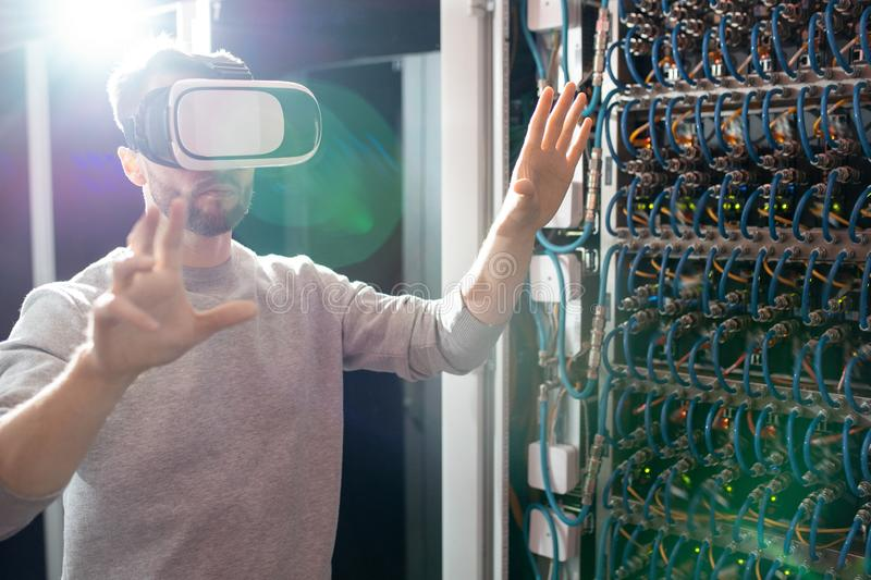 Engineer in VR goggles working in database center. Serious concentrated young bearded engineer in VR goggles standing in database center and gesturing hands royalty free stock photos