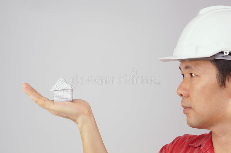 Engineer wear red shirt and white hat looking at house royalty free stock photo