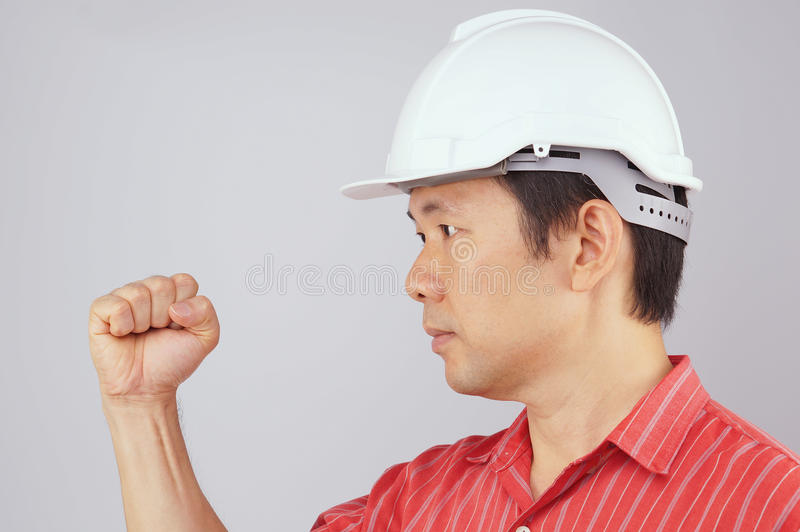 Engineer wear red shirt and white hat make signal fist royalty free stock photos