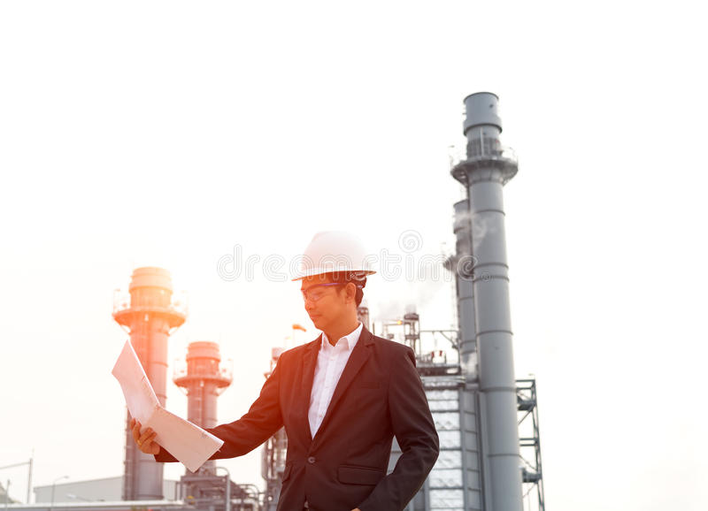 Engineer wearing white helmet holding paper drawing royalty free stock images