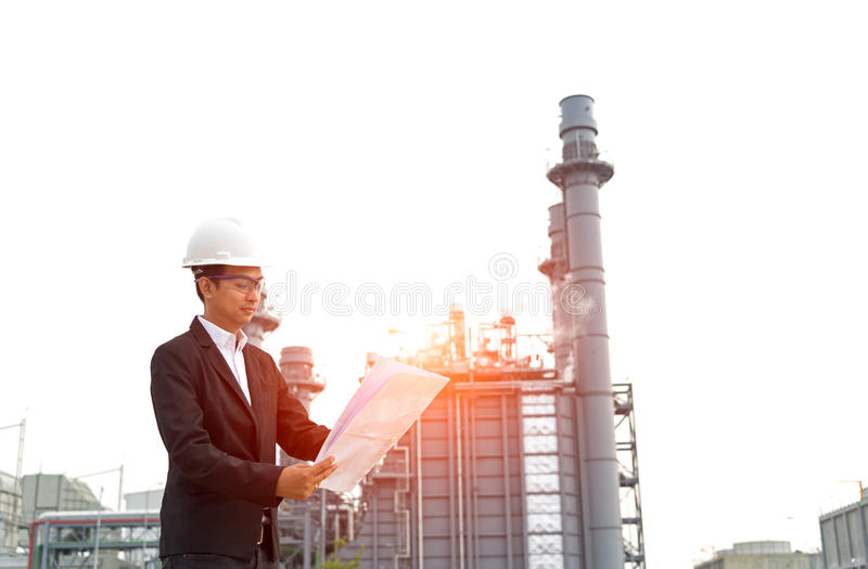 Engineer wearing white helmet holding paper drawing stock photo
