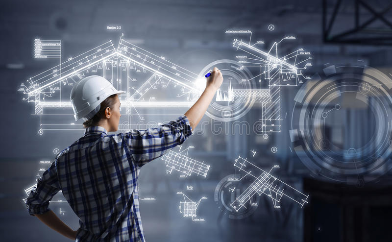 Engineer woman draw layout. Builder woman standing with back and drawing blueprints stock photography