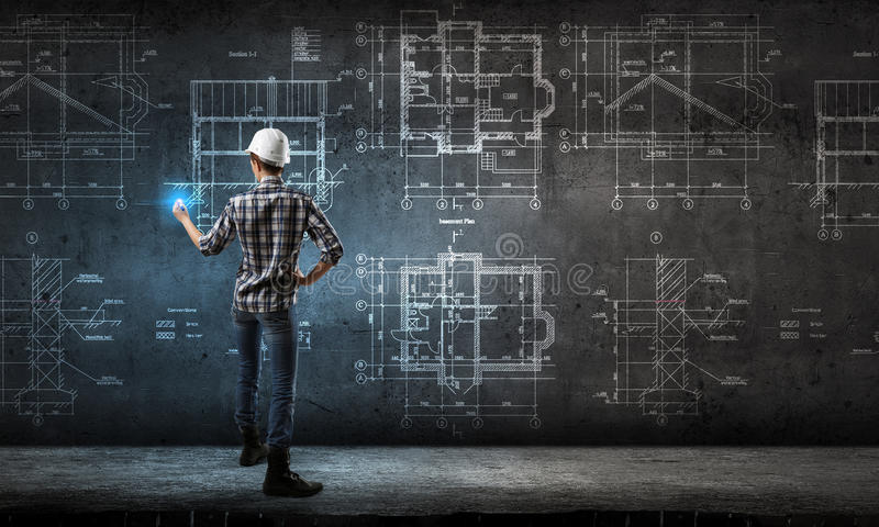 Engineer woman draw layout. Builder woman standing with back and drawing blueprints stock photo
