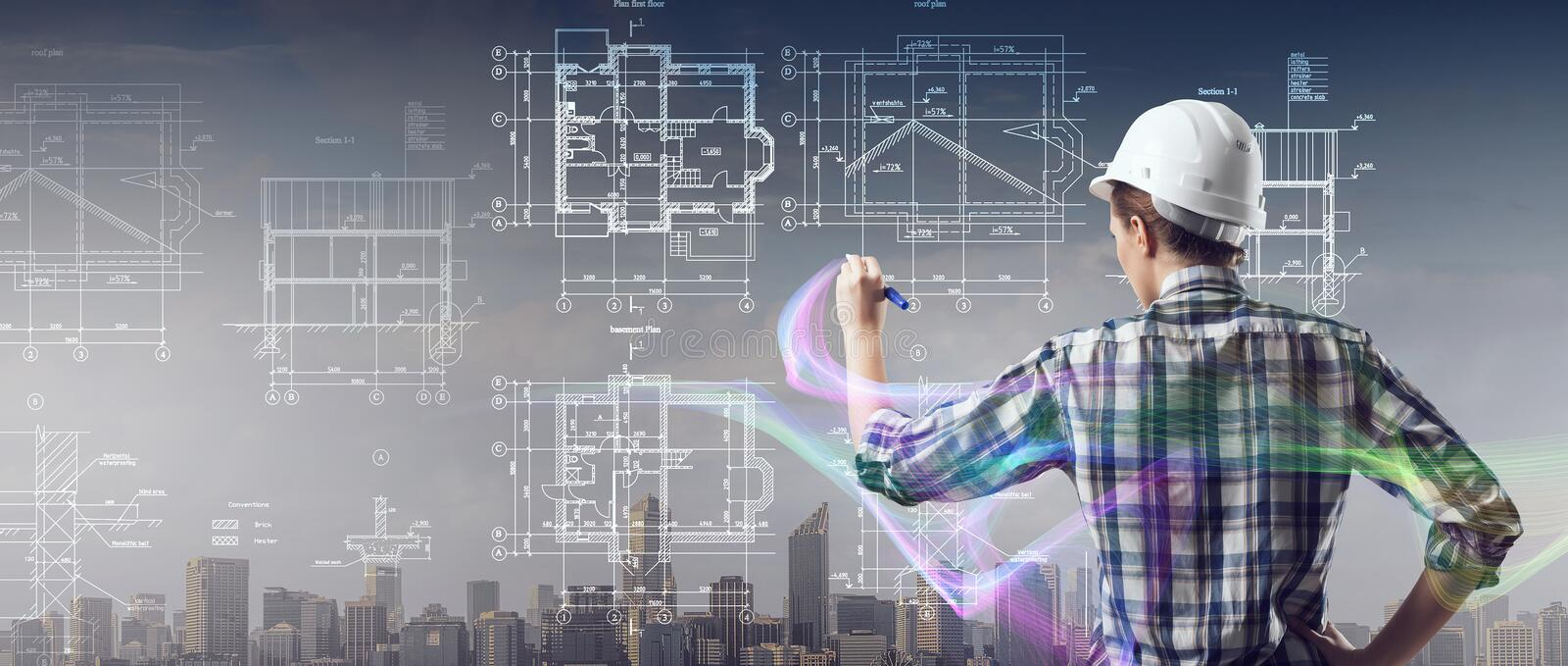 Engineer woman draw layout. Builder woman standing with back and drawing blueprints royalty free stock photography