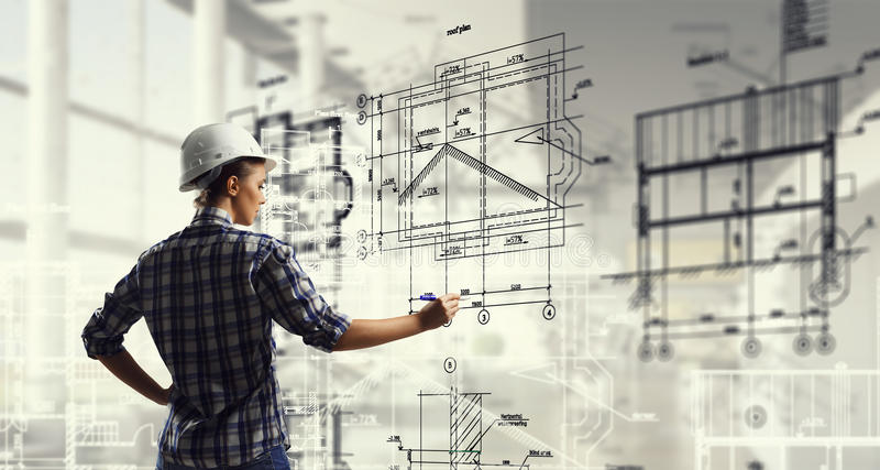 Engineer woman draw layout. Builder woman standing with back and drawing blueprints stock photos