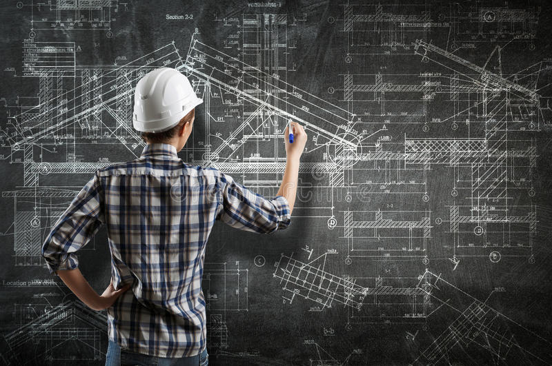 Engineer woman draw layout. Builder woman standing with back and drawing blueprints royalty free stock image