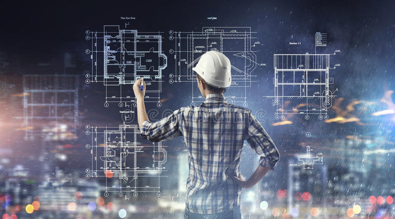 Engineer woman draw layout. Builder woman standing with back and drawing blueprints royalty free stock photos