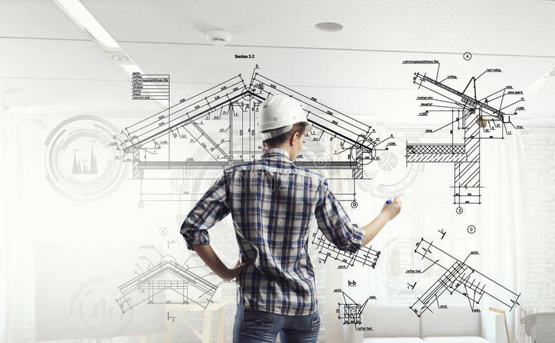 Engineer woman draw layout. Builder woman standing with back and drawing blueprints stock image
