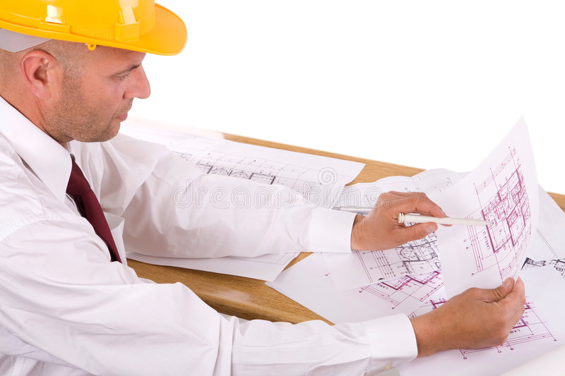 Engineer at work. Mature engineer looking at the construction blueprints royalty free stock photography