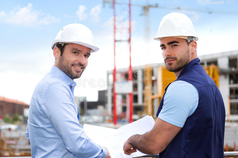 Engineer and worker checking plan on construction site royalty free stock photos