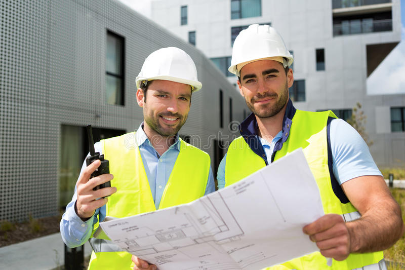 Engineer and worker checking plan on construction site royalty free stock images
