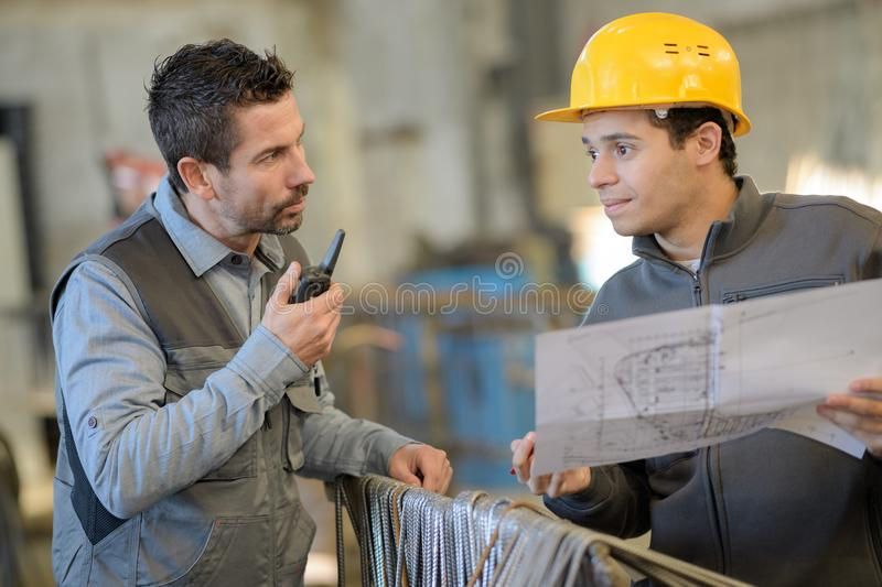 Engineer and worker checking plan on construction site stock images
