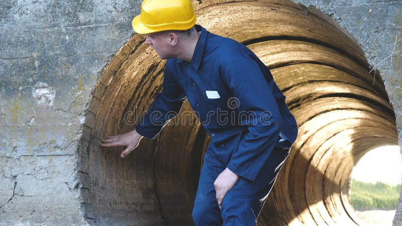 Engineer, worker checks gutters, in blue robe, in boots, in a construction yellow helmet, tunnels, technical supervision.  royalty free stock photo