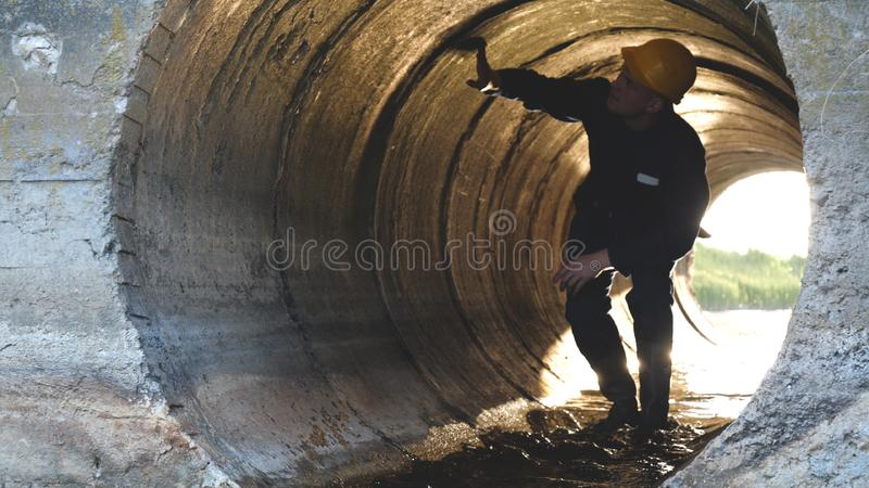 Engineer, worker checks gutters, in blue robe, in boots, in a construction yellow helmet, tunnels, technical supervision. stock image