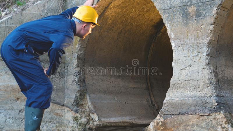 Engineer, worker checks gutters, in blue robe, in boots, in a construction yellow helmet, tunnels, technical supervision.  stock images