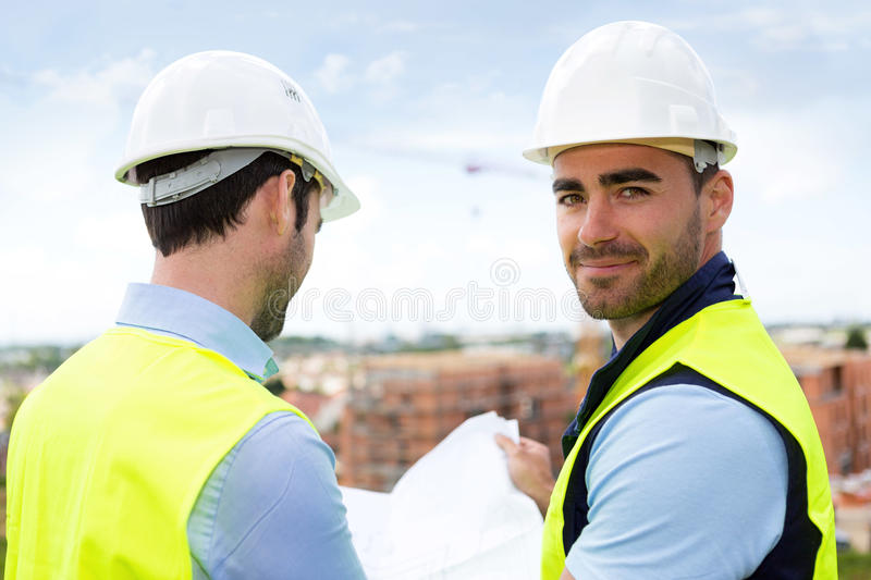 Engineer and worker watching blueprint on construction site stock download engineer and worker watching blueprint on construction site stock photo image of work malvernweather Image collections