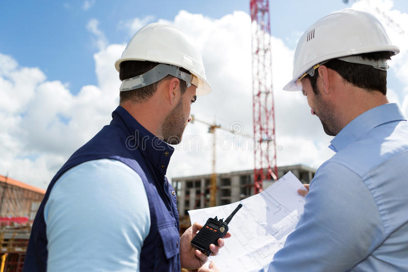 Engineer and worker watching blueprint on construction site stock image