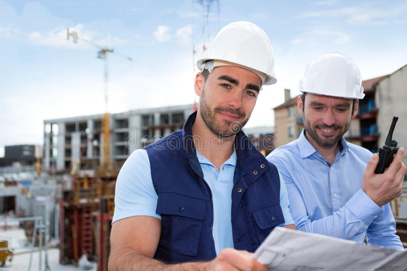Engineer and worker watching blueprint on construction site royalty free stock images