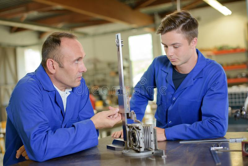 Engineer working with apprentice stock photos