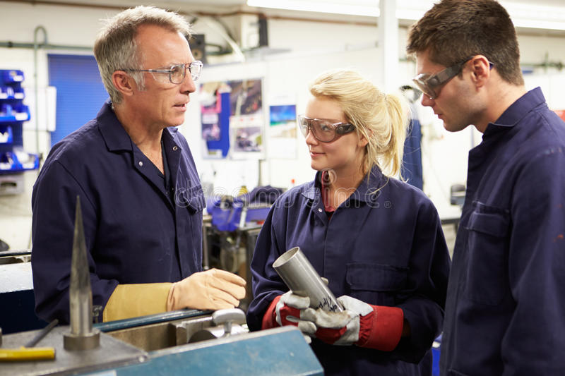 Engineer Working With Apprentices On Factory Floor. Having A Conversation stock image
