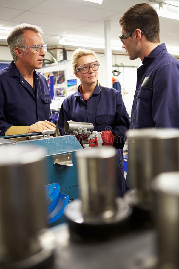 Engineer Working With Apprentices On Factory Floor stock images