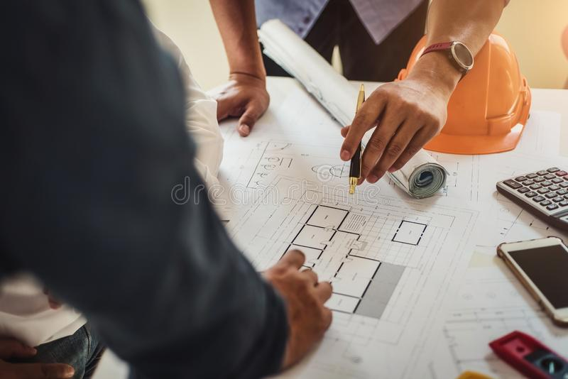 Engineer working at a blueprint of house in office for discussing real estate project. Engineering tools and construction concept stock images