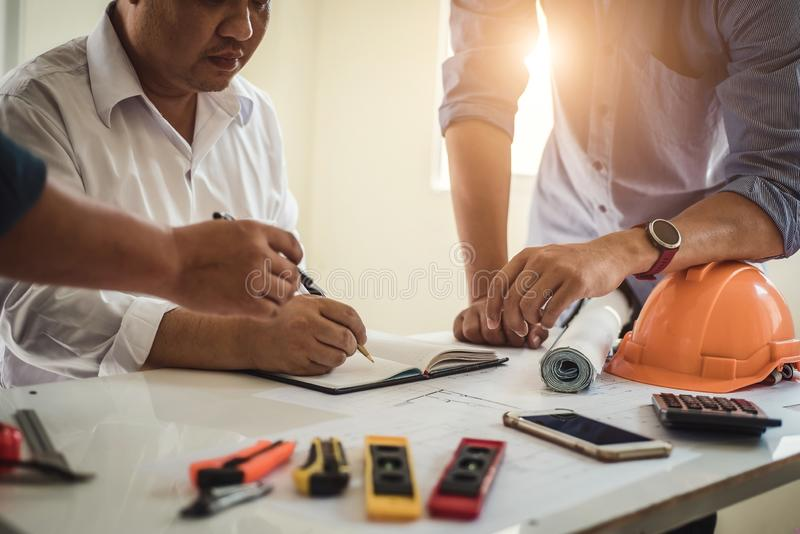 Engineer working at a blueprint of house in office for discussing real estate project. Engineering tools and construction concept stock image