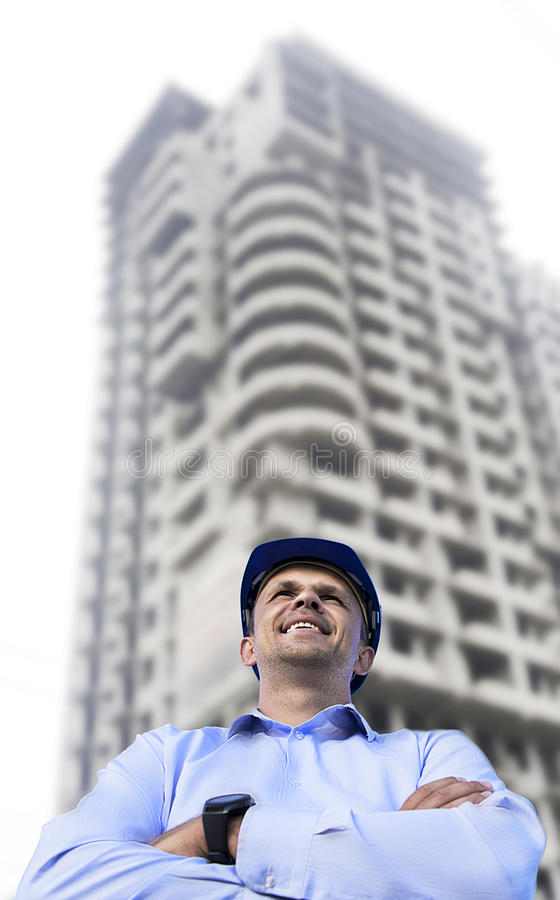 Engineer working on a building site wearing a protective helmet standing on the building background. royalty free stock photo
