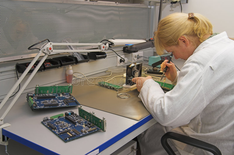 Engineer working with circuits. A woman engineer solders circuits sitting at a table