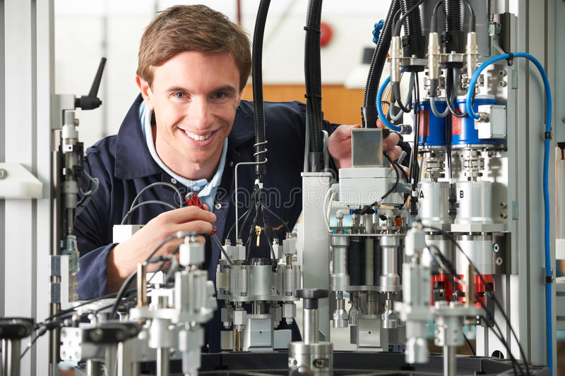 Engineer Working On Complex Equipment In Factory. Engineer Works On Machinery In Factory royalty free stock photos