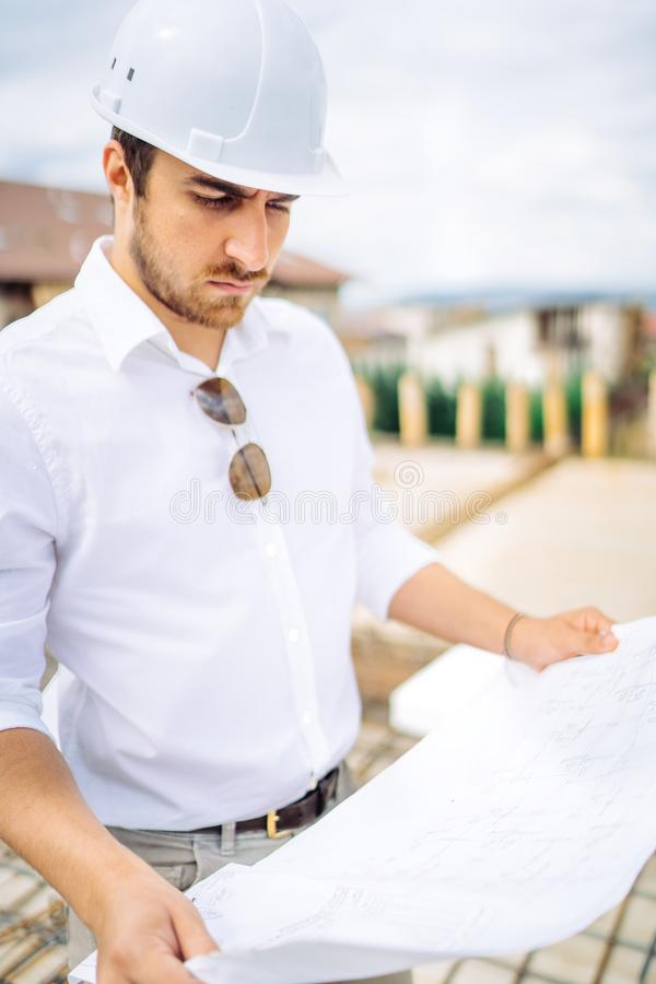 engineer working on construction site, reading building project and supervising works royalty free stock image