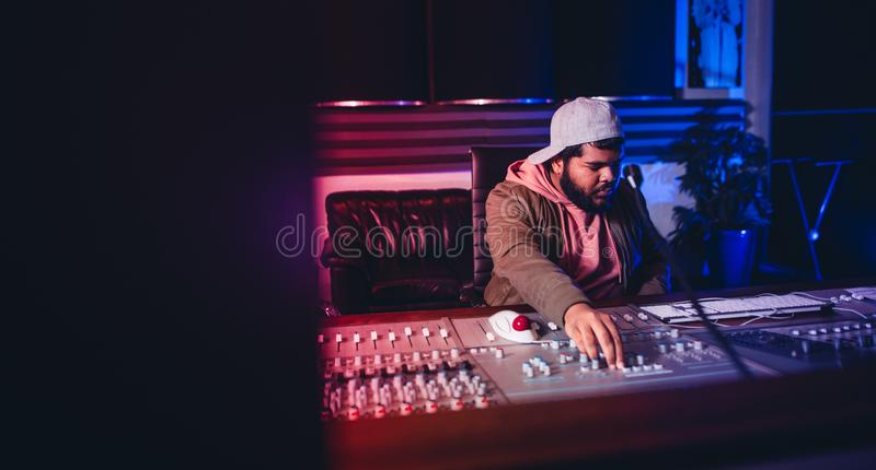 Engineer working on sound mixing desk in recording studio stock photo