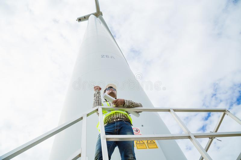 Engineer working at wind turbine site with blueprint stock image