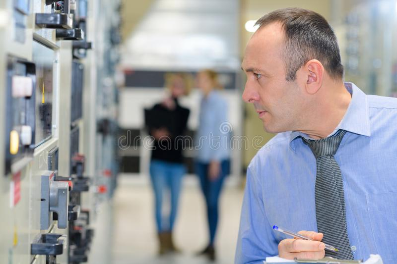 Engineer writing on clipboard in factory. Man royalty free stock photography