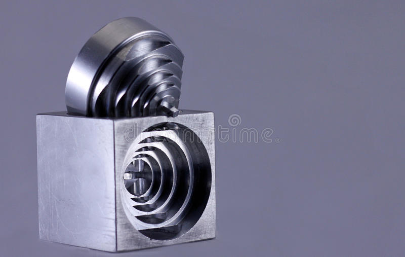 Engineered precision cut metal. Aluminum cube mechanically engineered to show a pattern royalty free stock photos