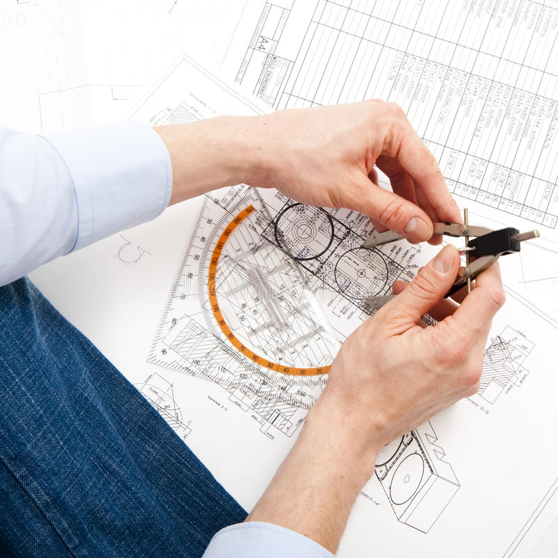 Engineering. An engineer checking a technical drawing with a pair of compasses and a triangle royalty free stock photography