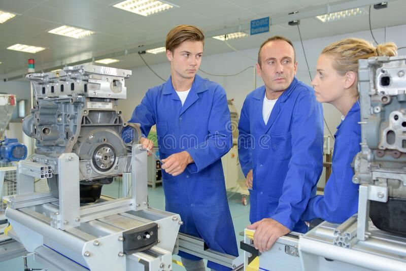 Engineering apprentices with instructor stock photography