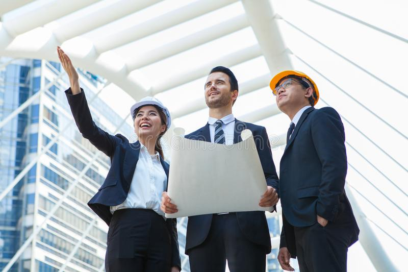 Engineering and architecture concept,engineers working on a building site holding a blueprints,architect man working with stock photos