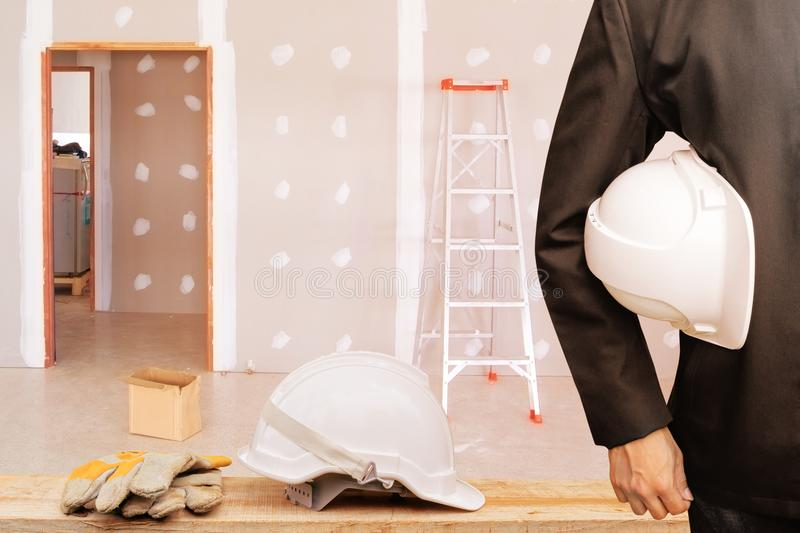 Engineering businessman holding helmet white in the work gypsum board wall interior. Decoration of home in construction site stock image