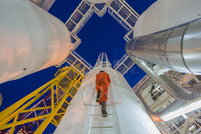 Engineering climb up to oil and gas process plant to observer gas dehydration processing in night shift. royalty free stock images