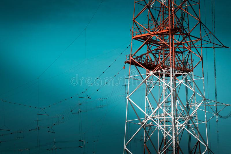 National Energy Grid system. Power pylons connecting the country. Red steel structures on deep blue sky royalty free stock photos
