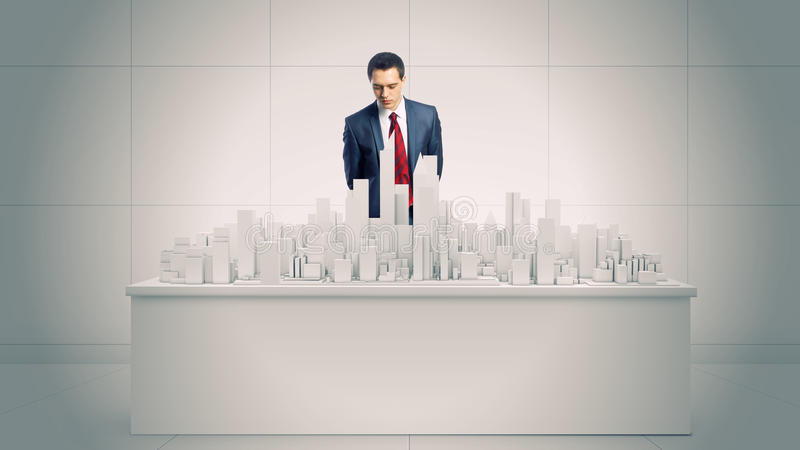 Engineering concept. Young businessman examining model of construction project royalty free stock photography