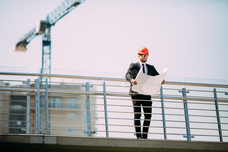Handsome man engineering consulting people on construction site download handsome man engineering consulting people on construction site holding blueprint in his hand building malvernweather Image collections