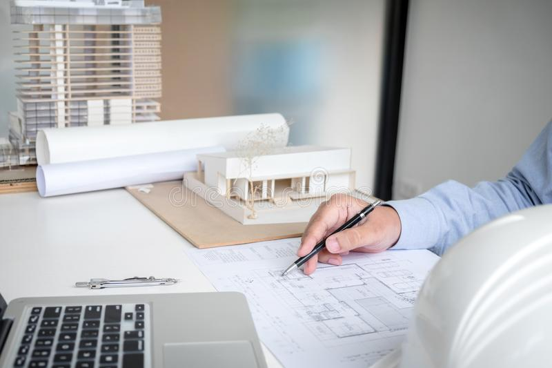 Engineering or Creative architect in construction project, Engineers hands working on construction blueprint and building model stock photo