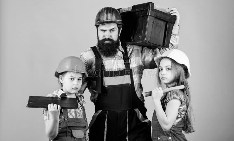 Engineering education. construction worker assistant. Father and daughter in workshop. Bearded man with little girls royalty free stock image