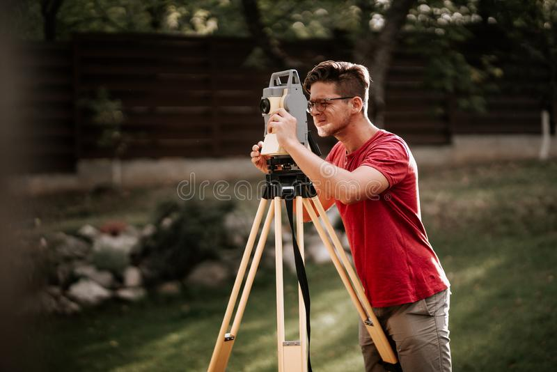 Engineering equipment with theodolite and total station in a garden working on coordinates. Surveyor engineering equipment with theodolite and total station in a royalty free stock photography