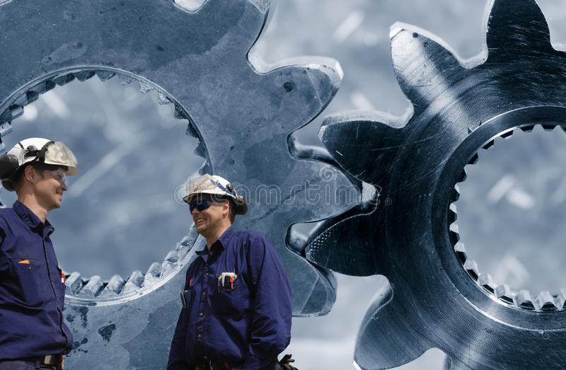 Engineering and gear parts. Two engineers, mechanics with giant gears, cogs in background stock photo