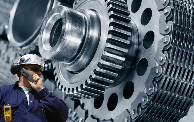 Engineering with giant machinery. Engineer, mechanic with large chain-powered cogwheels and gears in the background stock image