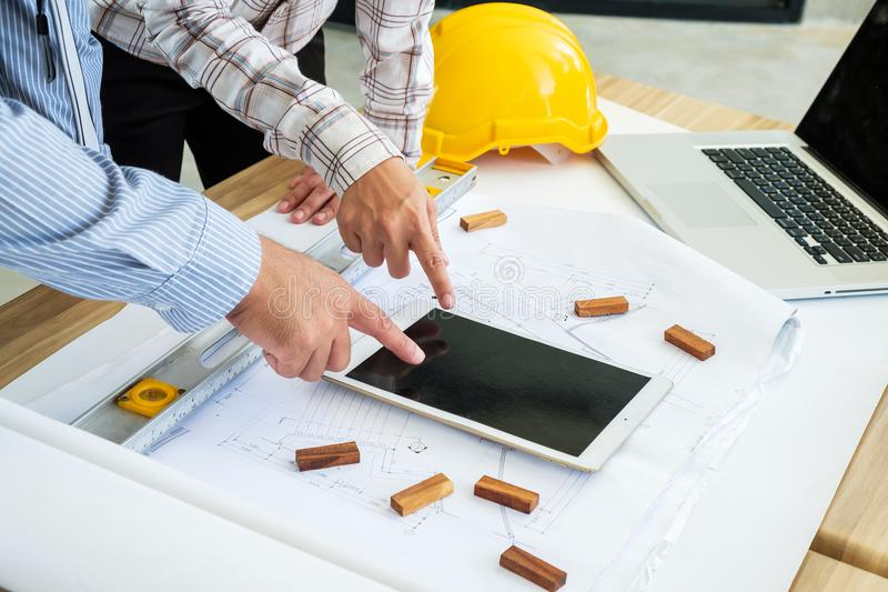 Engineering is looking tablet on a blueprint. To prepare for fie royalty free stock photo