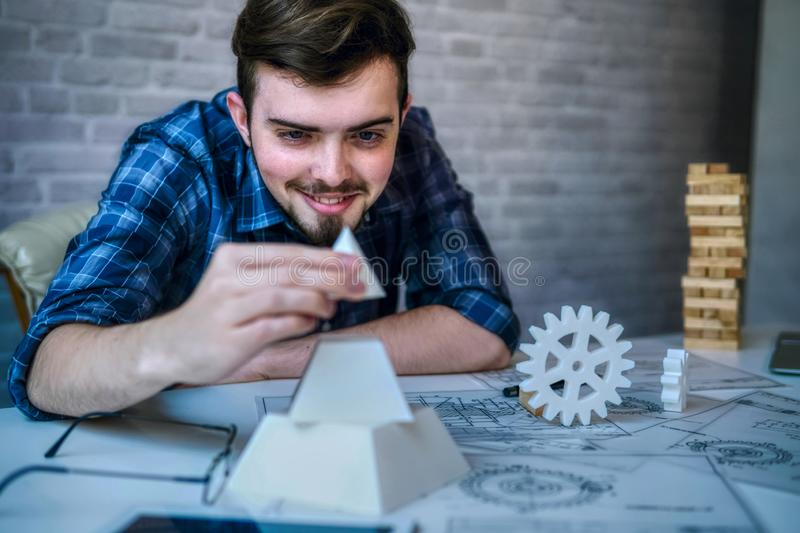 Engineering man` s hand working with 3D printer` s components and blueprint for designing mechanical parts . Engineering tools and technology business concept royalty free stock photography